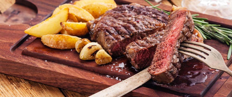 Chef slicing steak on cutting board